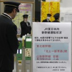 A station employee looks at a sign showing a suspension in bullet train services in northeastern Japan due to an earthquake, displayed at Nagano train station