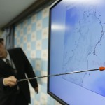 Japan Meteorological Agency's Senior Coordinator for Seismological Information Makoto Saito points to the spot showing the centre of a magnitude 7.3 earthquake, during a news conference in Tokyo