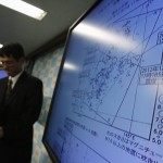 Japan Meteorological Agency's Senior Coordinator for Seismological Information Makoto Saito leaves next to a map showing earthquake epicentres occurring in 2011 and 2012, during a news conference in Tokyo