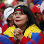 A follower of Venezuelan President Chavez reacts while gathering with other followers to express her support for him and to pray for his health at Plaza Bolivar in Caracas