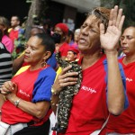 A woman holds a figurine of Venezuelan President Chavez, as she attends a mass to pray for Chavez's health in Caracas
