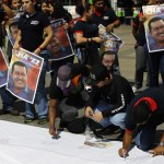 Supporters of Venezuelan President Hugo Chavez sign a giant poster in support of him in Caracas