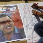 A supporter of Venezuelan President Hugo Chavez signs a giant poster in support of him in Caracas