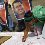 A supporter of Venezuelan President Chavez writes messages on a giant poster in support of him in Caracas