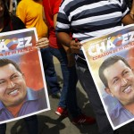 Supporters of Venezuelan President Chavez hold pictures of him, as they wait to write messages on a giant poster in support of him in Caracas