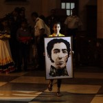 A girl carries a picture of Venezuelan national hero Simon Bolivar during a mass to pray for Venezuela's President Hugo Chavez in the Jesus de Miramar church in Havana