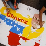 Followers of Venezuelan President Chavez paint a poster in support of him in Caracas