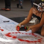 A follower of Venezuelan President Hugo Chavez paints on a giant poster in support of him in Caracas