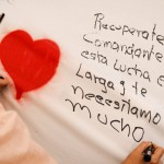 A supporter of Venezuelan President Hugo Chavez writes messages on a giant poster in support of him in Caracas