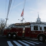 A flag is seen at half staff as a Newtown fire department truck passes along Main Street in Newtown, Connecticut