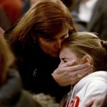 A woman comforts a young girl, during a vigil service for victims of the Sandy Hook Elementary School shooting in Newtown