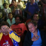 Supporters of Venezuelan President Hugo Chavez react while watching a government national TV broadcast with news about the president's health in Caracas