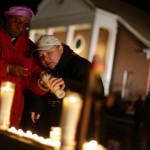 Two ladies light a candle outside Saint Rose of Lima Roman Catholic Church near Sandy Hook Elementary School, where a gunman opened fire on school children and staff in Newtown