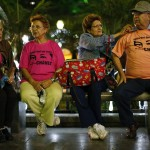 People wearing t-shirts supporting Venezuelan President Hugo Chavez sit on a bench at Plaza Bolivar in Caracas