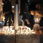 Mario Buda lights candles during a vigil commemorating victims of a Connecticut elementary school shooting in Oakland
