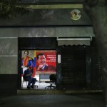 A man sits at the entrance of a building with a poster of Venezuelan President Hugo Chavez in Caracas