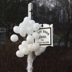 Balloons hang from the Sandy Hook School sign in Sandy Hook, Connecticut