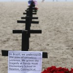 A resident runs near crosses planted by members of NGO Rio de Paz, in memory of victims of Sandy Hook Elementary school shooting in U.S., on Copacabana beach in Rio de Janeiro