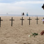 A woman puts flower near crosses planted by NGO Rio de Paz, in memory of victims of Sandy Hook Elementary school shooting in U.S., on Copacabana beach in Rio de Janeiro