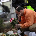 Dan Sullivan holds his hand to his face as he places flowers at a makeshift memorial in Newtown