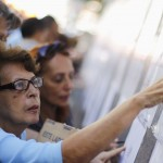 Venezuelans look for their identification number on lists outside a voting station during regional election in Caracas