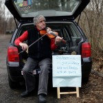 Man plays a violin along Church Hill Road in Newtown, Connecticut