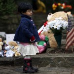 Girl stands near a makeshift memorial near the Sandy Hook Elementary School for the victims of a school shooting in Newtown, Connecticut