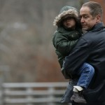 Father carrying a boy, pauses at a makeshift memorial near the Sandy Hook Elementary School for the victims of a school shooting in Newtown, Connecticut