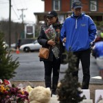 Couple pauses at a makeshift memorial near the Sandy Hook Elementary School for the victims of a school shooting in Newtown, Connecticut