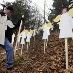 Eric Mueller places 27 wooden painted angels outside his home in Newtown, Connecticut