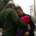 People react at a memorial near Sandy Hook Elementary School in Newtown