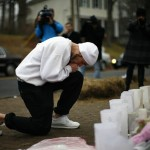 Man kneels at a memorial near Sandy Hook Elementary School in Newtown, Connecticut