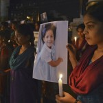 A woman holds a photo of a child during a vigil commemorating victims of a Connecticut elementary school shooting, in Bangalore