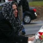 Woman grieves at a memorial near Sandy Hook Elementary School in Newtown, Connecticut