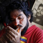 """Lopez, known as """"El Che"""", lights a cigar at his house in Caracas"""