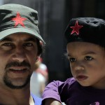 A father carrying his daughter poses for a picture while participating in a demonstration by a group of Montevideo's residents in support of Venezuela's President Chavez at Plaza Independencia square in Montevideo
