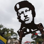 A supporter of Venezuelan President Chavez holds up wooden handicraft carving of Chavez's face outside Miraflores Palace in Caracas