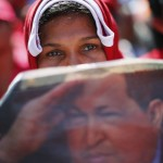A supporter of Venezuelan President Chavez holds a newspaper at rally outside Miraflores Palace in Caracas