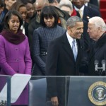 First lady Michelle Obama and daughter Malia watch as U.S. President Barack Obama is greeted by Vice President Biden as he arrives for his swearing-in ceremonies on the West Front of the U.S. Capitol in Washington
