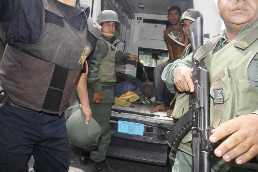 Soldiers prepare to evacuate unidentified injured victims during an uprising at Centro Occidental (Uribana) prison in Barquisimeto