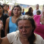 Relatives of inmates pray while protesting outside the Centro Occidental prison as an uprising occurs inside at Barquisimeto