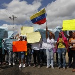 Relatives of inmates react as they hold posters to protest outside the Centro Occidental prison as an uprising occurs inside at Barquisimeto