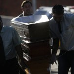 Funeral home workers arrive with empty coffins for victims of the fire at Boate Kiss nightclub before a collective wake in Santa Maria