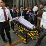 An injured person is transported on a stretcher outside the headquarters of state oil giant Pemex in Mexico City