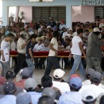 """Masked members of the """"Community Police"""", run by local residents of towns to police their communities, escort dozens of  prisoners onto a basketball court to face public trial, in the town of El Mezon"""