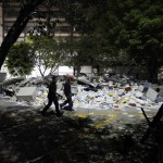 Rescue workers walk past debris piled outside the headquarters of state-owned oil giant Pemex in Mexico City