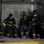 Firefighters take a break at the site of an explosion in the headquarters of state-owned oil giant Pemex in Mexico City