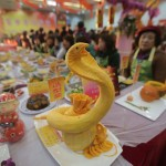 A dish created in the shape of a snake is presented on a table as residents stand around, during an annual local celebration for the upcoming Chinese New Year in Wuhan, Hubei province