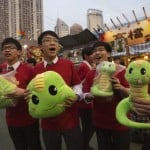 Shop assistants hold stuffed snake toys ahead of Lunar New Year celebrations at Victoria Park in Hong Kong