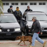 Neighbors walk their dog past US Marshals and La Palma Police providing security while detectives search the home of Christopher Dorner's mother after serving a search warrant in La Palma
